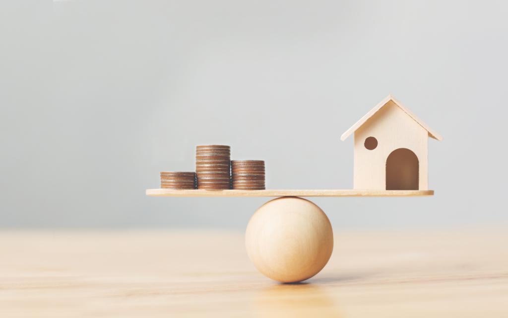 Eine Holzkugel auf der eine Holzplatte liegt worauf sich wiederum Geld und eine Modell-Haus befindet - beides vorsichtig ausbalanciert